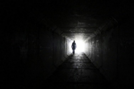 Picture of a person walking in tunnel with bright light at end