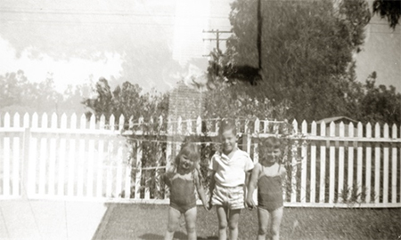 Old black and white summer-time photo of 3 children holding hands in front of white picked fence